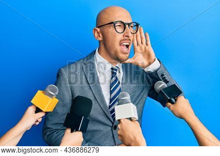 Bald man with beard being interviewed by reporters holding microphones shouting and screaming loud to side with hand on mouth. communication concept.