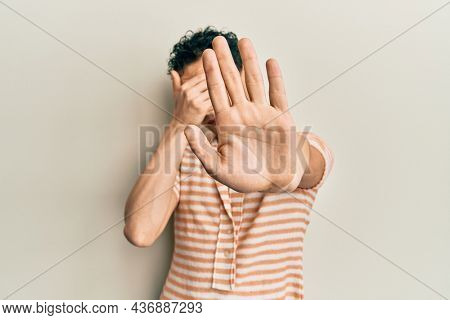 Handsome man wearing make up wearing casual t shirt covering eyes with hands and doing stop gesture with sad and fear expression. embarrassed and negative concept.