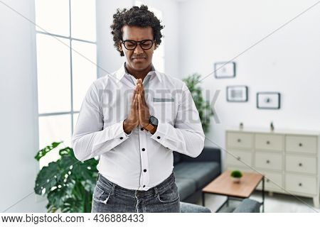 African psychologist man at consultation office begging and praying with hands together with hope expression on face very emotional and worried. begging.