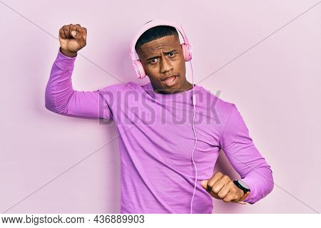 Young black man dancing listening to music using headphones in shock face, looking skeptical and sarcastic, surprised with open mouth