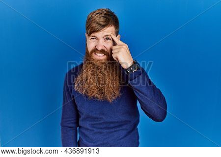 Redhead man with long beard wearing casual blue sweater over blue background pointing unhappy to pimple on forehead, ugly infection of blackhead. acne and skin problem