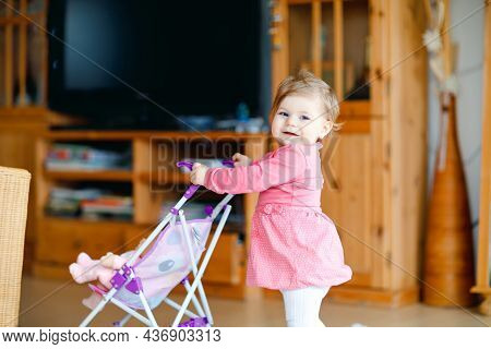 Cute Adorable Baby Girl Make First Steps And Push With Doll Carriage. Beautiful Toddler Child Pushin