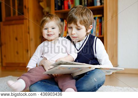 School Kid Boy Reading Book For Little Toddler Baby Girl, Two Siblings Sitting Together And Read Boo
