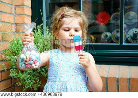 Little Preschool Girl With Bag With Bonbons And Lollipop. Cute Happy Toddler Child Licking Sweet Sug