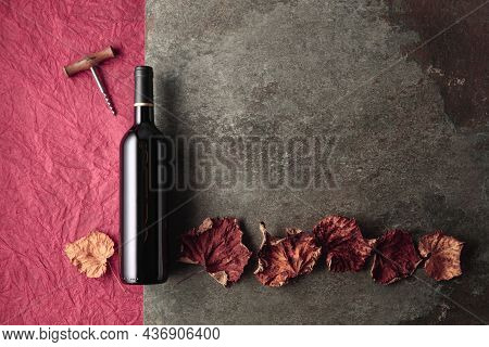 Bottle Of Red Wine With Corkscrew And Dried Vine Leaves On An Vintage Background. Top View With Copy