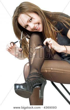 Smiling Girl With Scissors Cuts The Stockings. Isolated