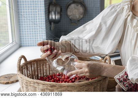 A Girl In Ethnic Clothes In The Kitchen, Puts Berries In A Glass Teapot. Basket With Hawthorn Berrie
