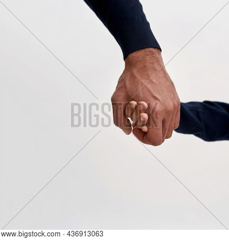 Narrow Vertical View Of Father And Son Holding Hands Isolated On White Studio Background. Dad And Bo