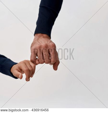 Crop Close Up Vertical Narrow Shot Of Loving Father And Small Son Hold Hands Little Finger Pinkie. C