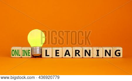 Online Learning Symbol. Wooden Cubes With Words Online Learning. Yellow Light Bulb. Beautiful Orange