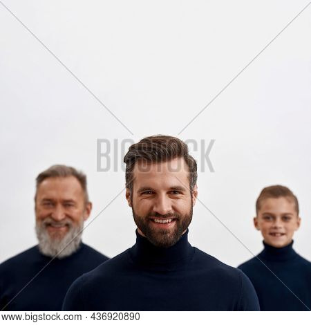 Portrait Of Smiling Young Man Forefront On White Studio Background, Small Son And Senior Father On B