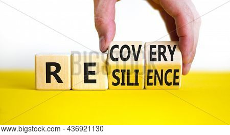 Recovery And Resilience Symbol. Businessman Turns Cubes And Changes The Word Recovery To Resilience.
