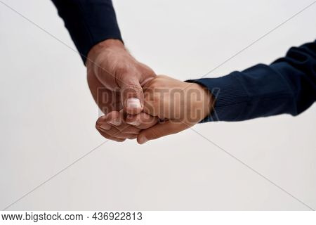 Close Up Crop Of Caring Father And Small Son Holding Hands Show Family Bonding, Unity And Support. L