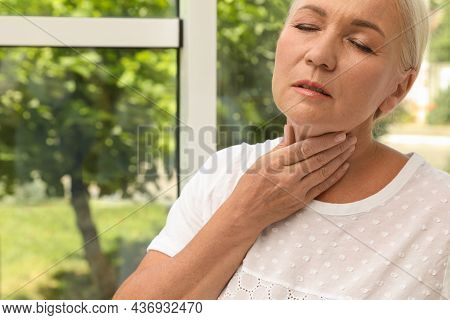 Mature Woman Doing Thyroid Self Examination Near Window, Closeup. Space For Text