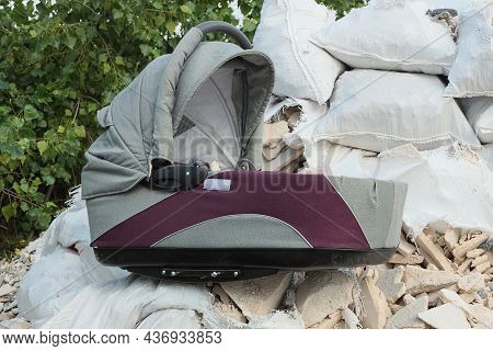 One Gray Purple Baby Carriage Stands On A Pile Of Rubbish From White Bags And Stones On The Street