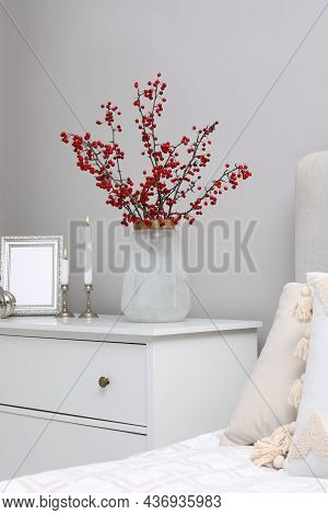 Hawthorn Branches With Red Berries, Candles And Frame On Chest Of Drawers In Bedroom