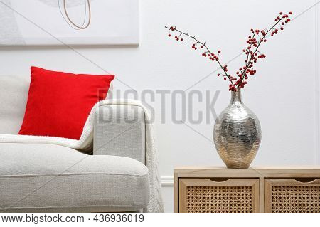 Hawthorn Branches With Red Berries On Wooden Commode In Living Room