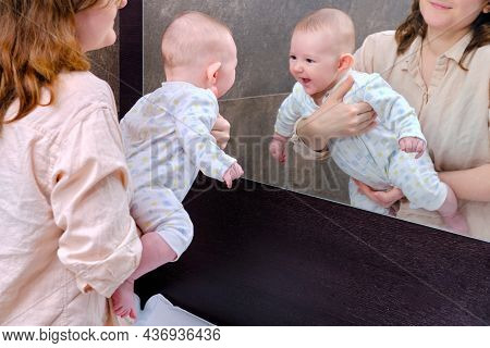 A Happy Baby In His Mother Arms Saw Himself In The Mirror And Laughs