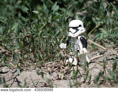 Chernihiv, Ukraine, July 13, 2021. A Walking Imperial Stormtrooper Among Plants, A Plastic Minifigur