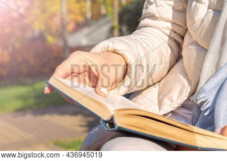 Unrecognizable Caucasian Woman In Casual Clothes Sitting On Park Bench And Reading Real Paper Book.
