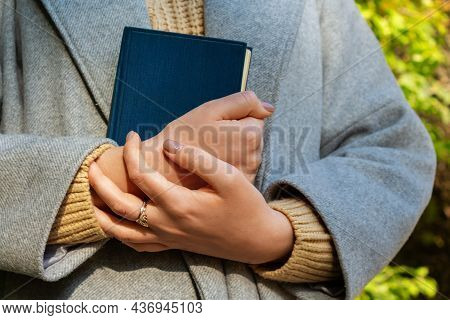 Young Unrecognizable Caucasian Woman In Grey Coat Holding Old Blue Vintage Book. Autumn In Park. Aut