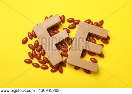 Wooden Letters Fe And Pills On Yellow Background, Flat Lay. Anemia Treatment