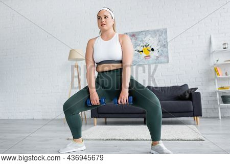 Plus Size Woman Doing Squat While Training With Dumbbells At Home