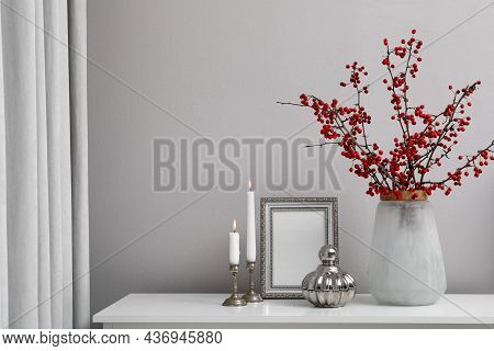 Hawthorn Branches With Red Berries In Vase, Candles And Frame On Table Indoors, Space For Text