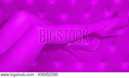 Female Legs In Purple Shoes In Purple Tights On A Purple Monochrome Background