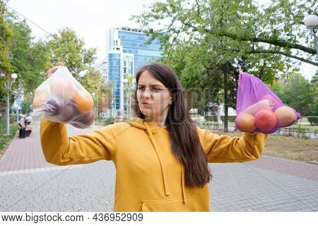 The Woman Keeps Vegetables And Fruits In A Plastic Bag And A Cloth Shopper.