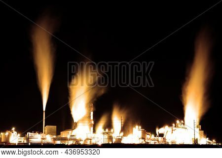 Old factory pumping out pollution and steam through smokestack at night with bright lights