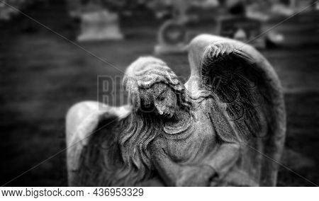 Gravestone grave stone headstone in cemetery angel statue grief and remembrance wings and prayer