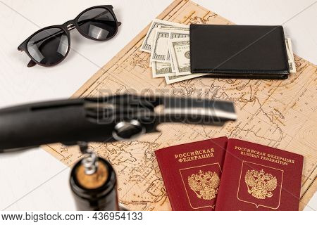 The Neck Of A Bottle Of Red Wine With A Corkscrew In The Cork, A Map Of The World, Two Passports, Mo