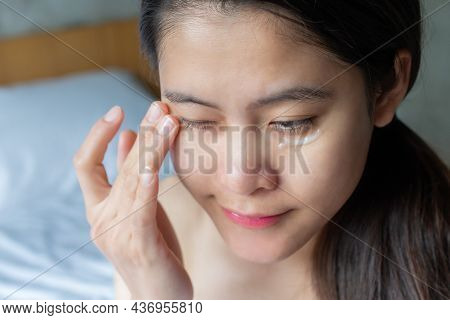 Asian Woman Applying Anti Aging Cream On Her Under Eyes. The Anti Aging Cream Is Using To Reducing,