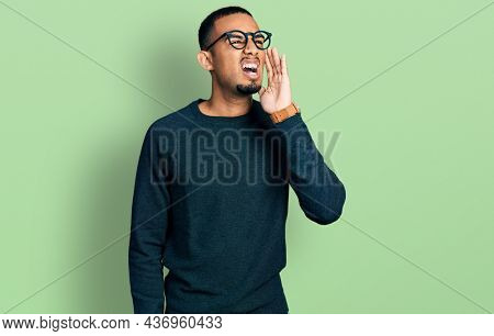 Young african american man wearing casual clothes and glasses shouting and screaming loud to side with hand on mouth. communication concept.
