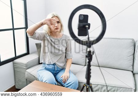 Young caucasian woman recording vlog tutorial with smartphone at home looking unhappy and angry showing rejection and negative with thumbs down gesture. bad expression.