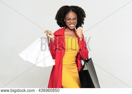 Black woman grimacing while posing with shopping bags isolated over white background