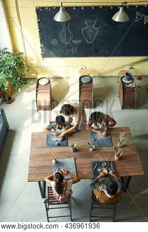 Directly above view of multi-ethnic children making handmade pots under control of teacher at pottery class
