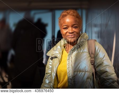 Portrait of happy young urban black African American woman smiling in city crowd, looking at camera.