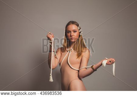 Fashion Girl With Rope Strap On Her Body At Grey Background