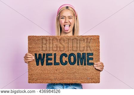 Beautiful blonde woman holding welcome doormat sticking tongue out happy with funny expression.