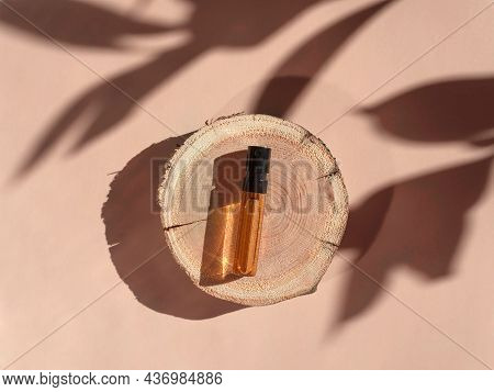Perfume Sample With Yellow Liquid On Wooden Tray Lying On Beige Background With Shadows Above. Luxur