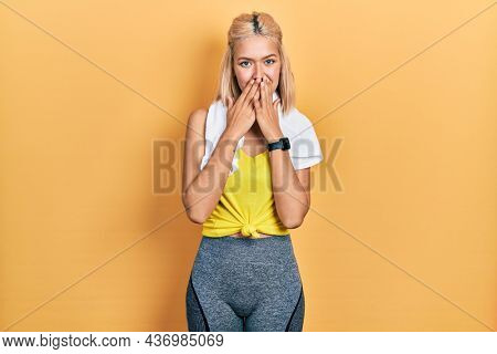 Beautiful blonde sports woman wearing workout outfit laughing and embarrassed giggle covering mouth with hands, gossip and scandal concept