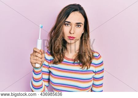 Young hispanic girl holding electric toothbrush thinking attitude and sober expression looking self confident