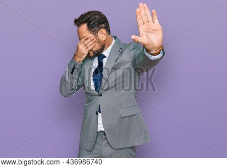Middle age man wearing business clothes covering eyes with hands and doing stop gesture with sad and fear expression. embarrassed and negative concept.