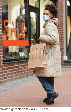 Brunette African American Woman In Medical Mask Doing Christmas Shopping In Mall