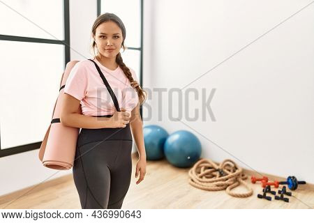 Young beautiful woman at the gym wearing sportswear holding yoga mat thinking attitude and sober expression looking self confident