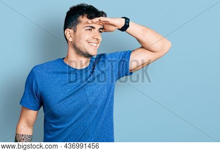 Young hispanic man wearing casual t shirt very happy and smiling looking far away with hand over head. searching concept.