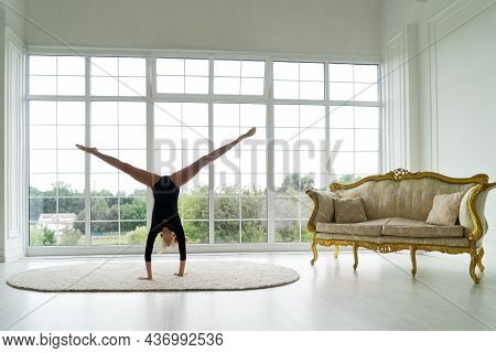 Teenage Girl Gymnast In Sport Bodysuit Makes Gymnastics And Stretching Routine By Raising Legs Up An