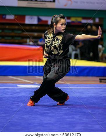 KUALA LUMPUR - NOV 03: Tan Yan Ni of Singapore shows her fighting style in the 'changquan compulsory' event at the 12th World Wushu Championship on November 03, 2013 in Kuala Lumpur, Malaysia.